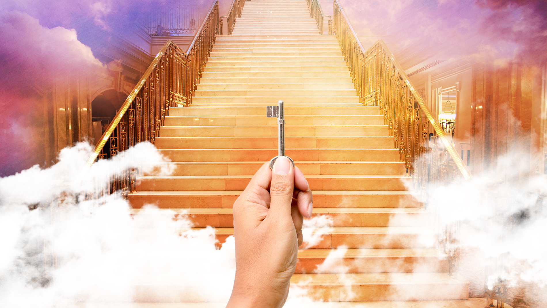 Hand holding a key in front of a staircase